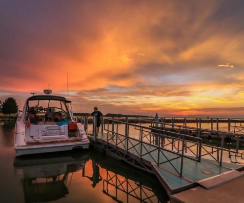Man docking his boat, Serenity, at sunset